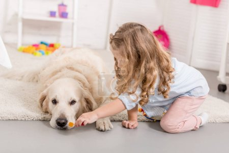 Photo for Adorable kid pretending veterinarian and examining cute golden retriever in children room - Royalty Free Image