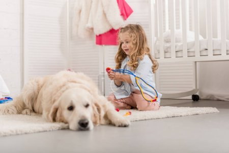 Photo for Selective focus of adorable kid pretending veterinarian and examining golden retriever in children room - Royalty Free Image