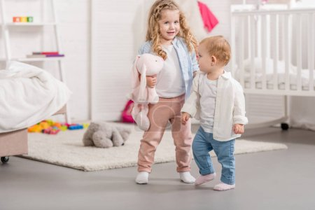 Photo for Adorable sisters standing in children room - Royalty Free Image