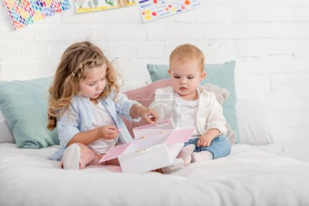 Photo for Adorable preschooler and toddler sisters playing on bed in children room - Royalty Free Image