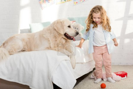 Foto de Adorable kid standing near bed with dog in children room - Imagen libre de derechos
