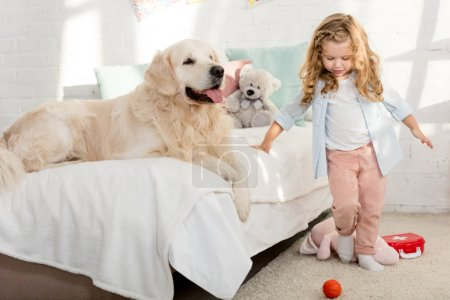Photo for Adorable child standing near bed with dog in children room - Royalty Free Image