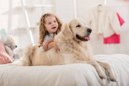 Photo for Adorable kid and dog lying on bed in children room - Royalty Free Image