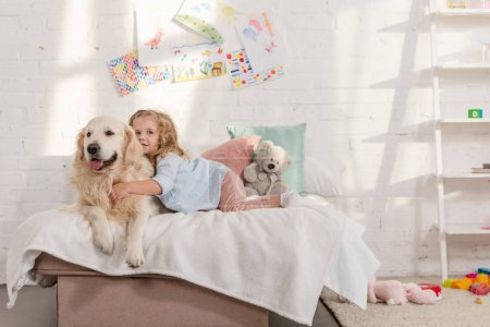 Photo for Adorable child and golden retriever lying on bed in children room - Royalty Free Image