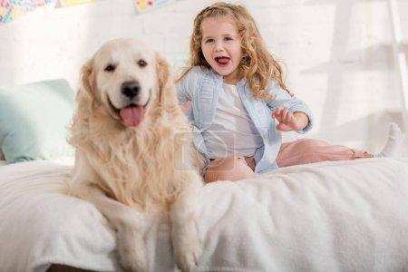 Foto de Excited adorable kid and golden retriever sticking tongues out together on bed in children room - Imagen libre de derechos