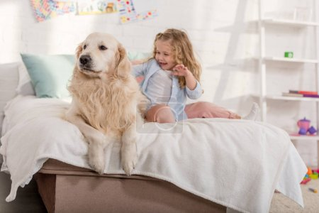 Photo for Happy adorable kid palming golden retriever on bed together in children room - Royalty Free Image
