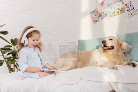 Photo for Adorable child listening music with tablet, golden retriever lying on bed in children room - Royalty Free Image