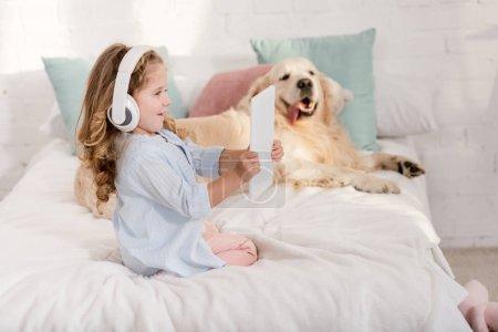 Foto de Happy adorable kid listening music with tablet, golden retriever lying on bed in children room - Imagen libre de derechos