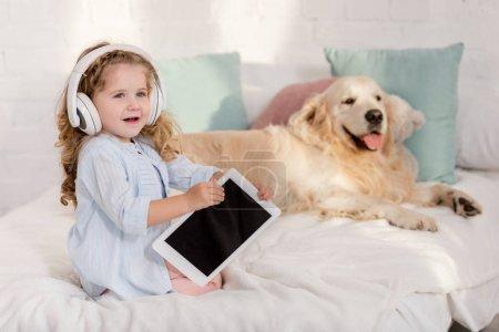 Photo pour Musique écoute gamin adorable avec tablette, moelleux retriever golden allongé sur le lit dans la chambre d'enfants - image libre de droit