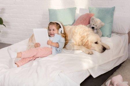 Photo pour Heureux enfant adorable musique avec tablette et penché dans golden retriever sur lit dans la chambre d'enfants - image libre de droit