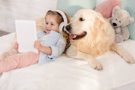 Photo for Adorable child listening music with tablet and leaning on cute golden retriever on bed in children room - Royalty Free Image
