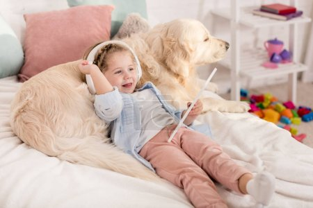 Photo for Adorable kid using tablet and leaning on golden retriever on bed in children room - Royalty Free Image