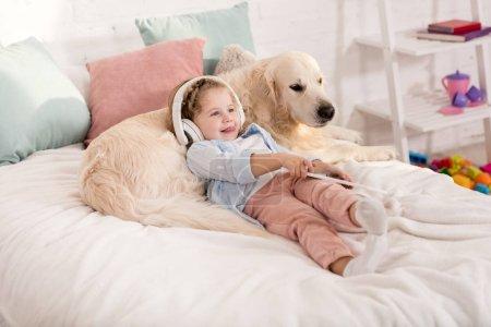 Foto de Adorable kid listening music with tablet and leaning on fluffy golden retriever on bed in children room - Imagen libre de derechos