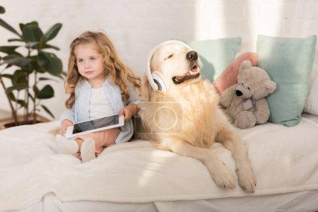 Photo pour Tablette de tenue adorable gamin, golden retriever avec casque allongé sur le lit dans la chambre d'enfants - image libre de droit