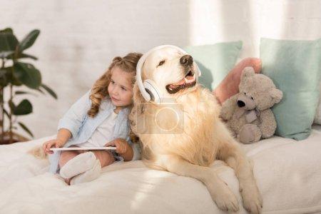 Photo pour Adorable enfant tenant tablet, mignon golden retriever avec casque allongé sur le lit dans la chambre d'enfants - image libre de droit