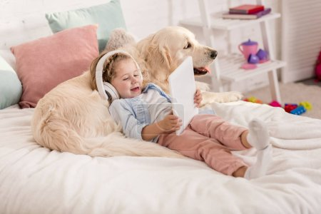 Photo for Adorable happy kid listening music with tablet and leaning on golden retriever dog on bed in children room - Royalty Free Image