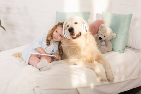 Photo for Adorable kid holding tablet and leaning on golden retriever with headphones lying on bed in children room - Royalty Free Image