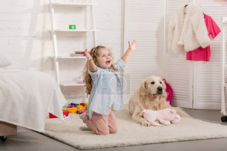 happy adorable kid standing on knees with open arms, golden retriever lying on carpet in children room