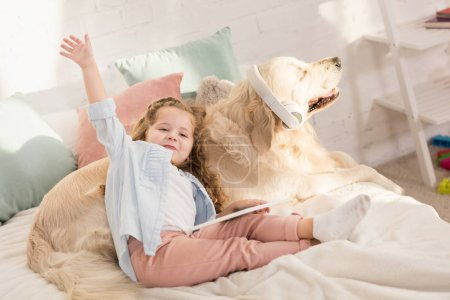 Photo for Adorable kid holding tablet and waving hand, golden retriever with headphones lying on bed in children room - Royalty Free Image