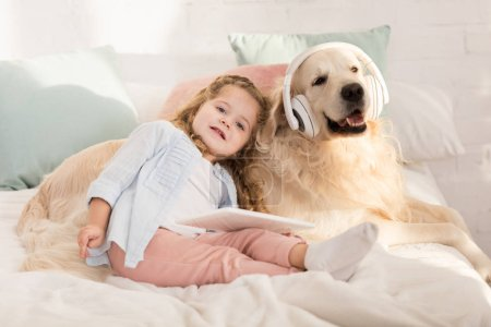 Photo for Adorable kid holding tablet and leaning on cute golden retriever with headphones lying on bed in children room - Royalty Free Image