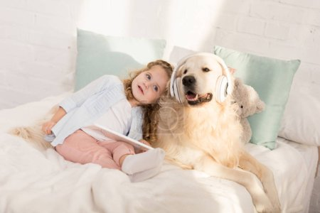 Photo for Adorable child holding tablet and leaning on fluffy golden retriever with headphones lying on bed in children room - Royalty Free Image