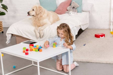 Photo for High angle view of adorable kid playing with educational cubes, golden retriever lying on bed in children room - Royalty Free Image