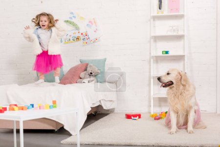 Photo for Excited adorable kid jumping on bed, golden retriever sitting on carpet in pink skirt in children room - Royalty Free Image