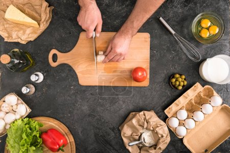 Photo for Cropped view of man chopping mushroom on cutting board with pizza ingredients on grey background - Royalty Free Image