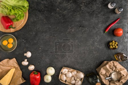 top view of pizza ingredients with copy space on grey textured background