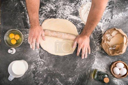 abgeschnittene Ansicht eines Mannes, der Pizzateig mit Holznadel auf grauem Hintergrund rollt