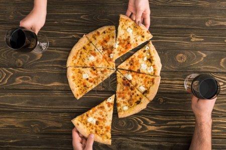 Photo pour Vue dégagée du couple en train de dîner avec pizza au fromage et vin rouge à table en bois - image libre de droit