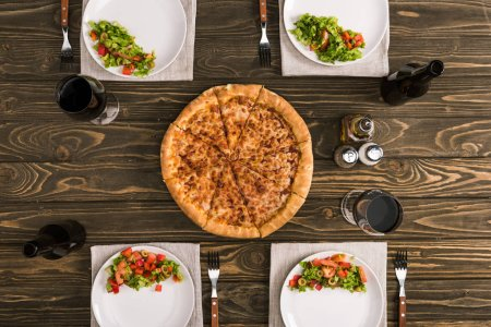 table setting with pizza and glasses of wine on wooden table