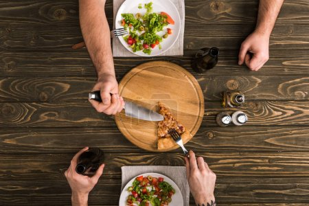 cropped view of men sharing pizza slice with knife and fork at wooden table