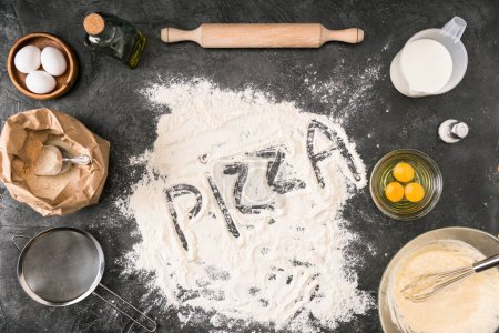 Photo for Top view of 'pizza' word made of flour with ingredients and cooking utensils on grey background - Royalty Free Image