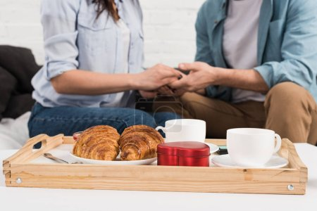 selective focus of breakfast food tray with couple sitting and holding hands on background