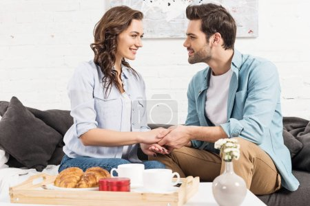 smiling couple sitting on couch, looking at each other and holding hands while having breakfast at home