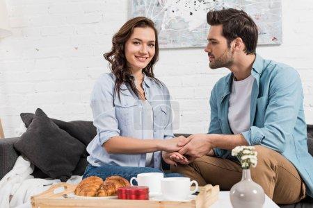 Photo pour Couple assis sur le canapé et tenant la main tout en prenant le petit déjeuner à la maison - image libre de droit