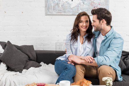 Foto de Sonriente pareja sentado en sofá y cogidos de la mano en la sala de estar - Imagen libre de derechos