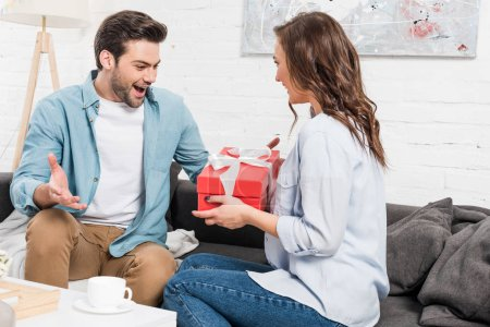 woman sitting on couch and presenting birthday gift box to surprised man in living room