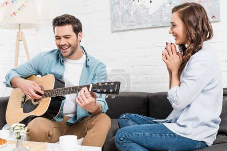 Photo for Woman sitting on couch and listening man performing with acoustic guitar at home - Royalty Free Image
