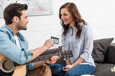 man with acoustic guitar sitting on couch and giving vintage audio cassette to beautiful woman at home