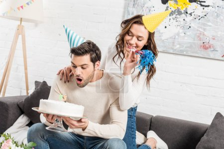 man blowing out candles on birthday cake while woman cheering with party horn at home
