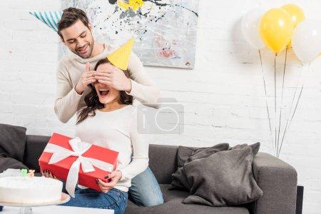 man surprising excited woman with birthday gift in living room