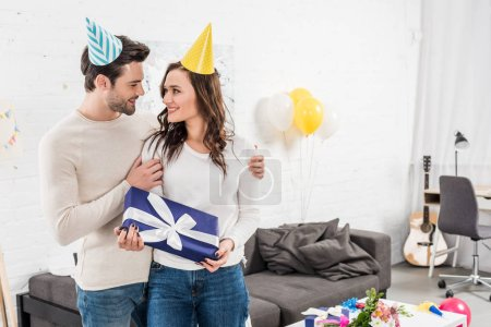 happy couple in party hats looking at each other, embracing and holding birthday present in living room