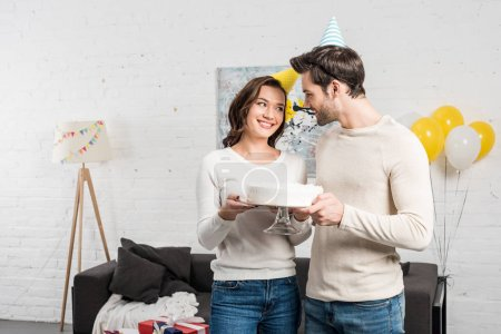happy couple in party hats holding cake and celebrating birthday in living room