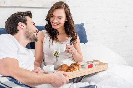 Foto de Sonriente pareja acostado en la cama y tener el desayuno en la mañana - Imagen libre de derechos