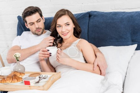 Foto de Hermosa pareja acostado en la cama y desayuno en la mañana - Imagen libre de derechos