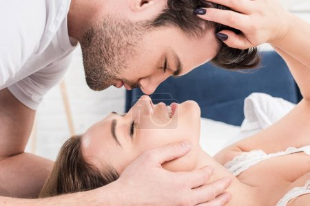 close up of couple with eyes closed touching each other in bed