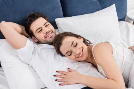 beautiful smiling couple cuddling in bed at home