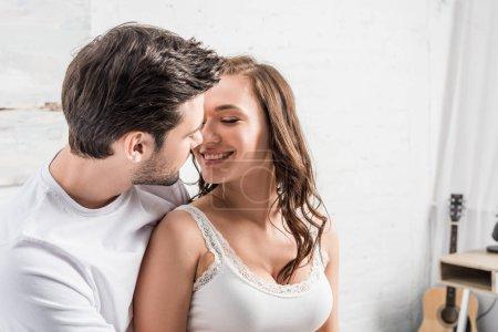 Photo pour Couple tendrement embrasser et regardant les uns les autres dans son lit - image libre de droit